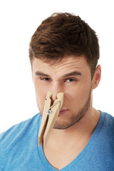Young man with clothespin on his nose.