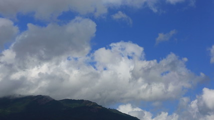 Clouds quickly float over low mountain