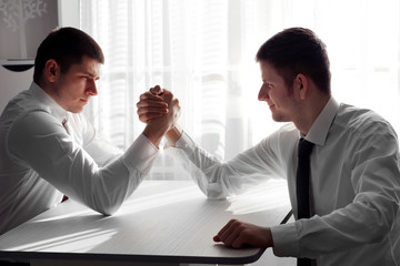 Arm wrestling of business people in office