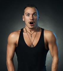 Surprised sporty man on black background