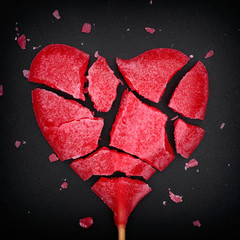 Broken red heart shaped lollipop