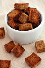 Rye homemade croutons in a white bowl
