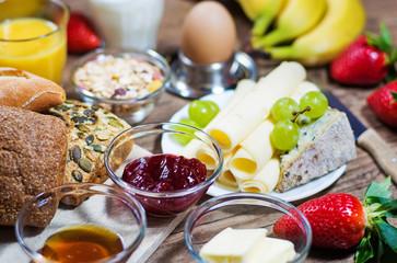 bunter Frühstückstisch mit Brötchen, Obst und Käse