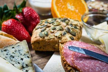 Früchstückstisch mit Brötchen, Käse,  Wurst und Obst