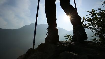 hiker legs on mountain peak rock