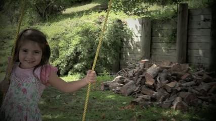 Slow motion of little girl swinging on a swing