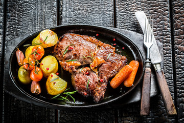 Roasted vegetables and steak with fresh herbs on grill