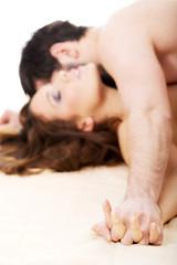 Man kissing woman in bedroom.