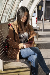 young latina girl in the street with mobile phone