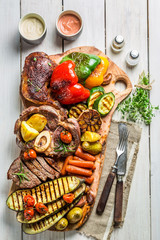 Grilled vegetables and steak with salt on wooden board