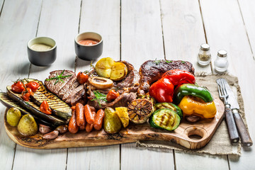 Grilled steak and vegetables with salt on wooden board