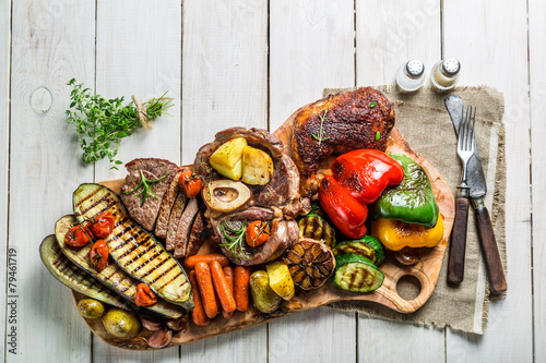 Roasted vegetables and steak with herbs on white table