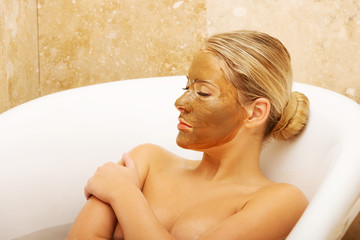 Woman relaxing in bath with chocolate mask on face