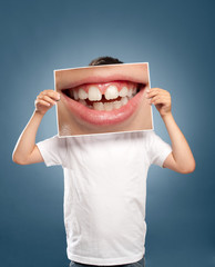 kid holding a picture of a mouth smiling