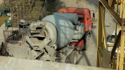 Truck with cement mixer preparing base for concreting building