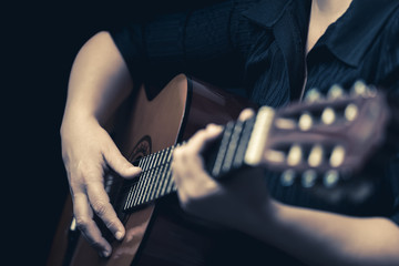 Musician hands playing an acoustic guitar