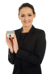 Businesswoman holding house model.
