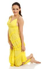 Beautiful woman kneelin in yellow dress.