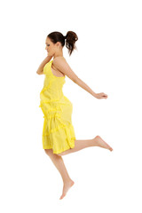 Beautiful woman jumping in yellow dress.