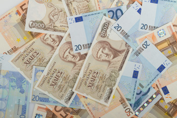 Old Greek 1000 drachmas banknotes and euro bills.
