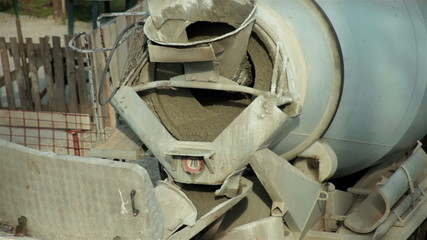 Truck with cement mixer preparing base for concreting, close up.