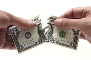 Dollar bill being torn in half