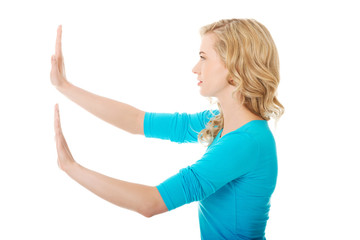 Side view woman pulling imaginary screen