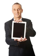 Happy businessman holding digital tablet