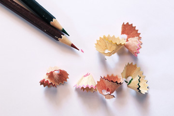 Pencils and pencil shaves on white paper
