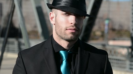 a rather sinister looking young man in a suit and hat