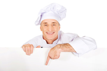Chef in white uniform holding empty banner