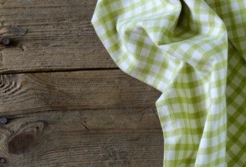 Wooden background with checkered kitchen towel