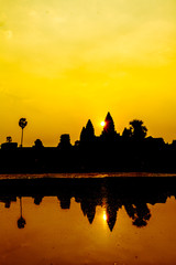 Angkor Wat at sunrise seen across the lake, reflected in water