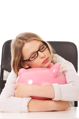 Young woman with piggybank on the desk