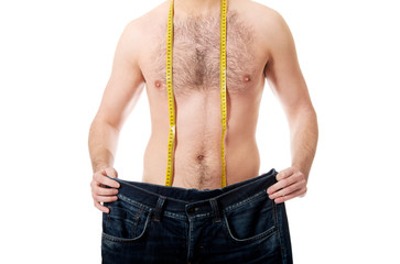 Man with oversized jeans and measure tape.