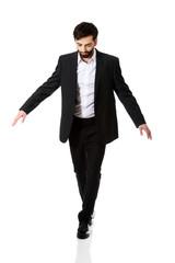 Businessman walking carefully.