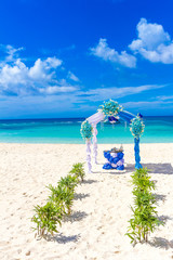 beautiful decorated wedding arch on sand beach, outdoor tropical