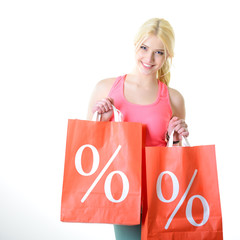 Beautiful cheerful young woman with colored sale shopping bags o
