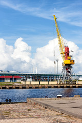 Cargo crane in the port of the Baltic against the blue sky in su
