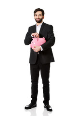 Businessman putting a coin to piggy bank.
