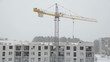 Постер, плакат: Crane lift block house part and builders work in heavy blizzard