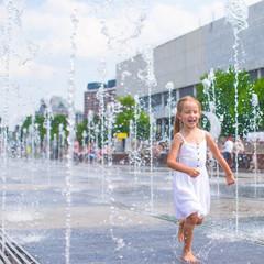 Cute girl having fun in outdoor fountain at hot day