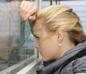Junge Frau schaut in zerbrochene Fensterscheibe