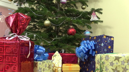 Heap of gifts presents boxes under decorated christmas fir tree
