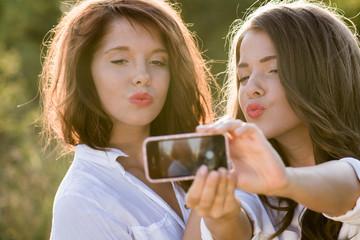 Two beautiful young women making selfie and grimacing