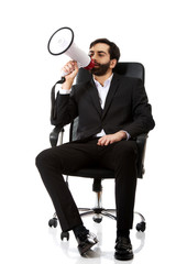 Businessman sitting on armchair with megaphone.
