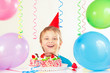 Young boy in festive hat with a birthday cake and balloons
