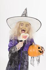 Mädchen mit Halloween Laterne und essen Süßigkeiten