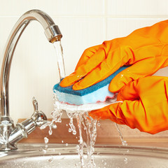 Hands in rubber gloves wash the dirty plate under running water