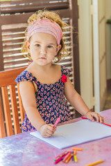 young beautiful child girl drawing at home on natural outdoor gr